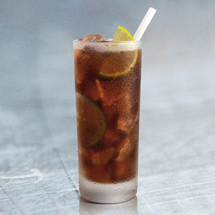 Clan Cervecero - cuba libre bebida alcohólica en una vaso de vidrio con hielo, rodajas de limón en fondo gris.